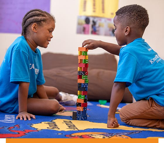 Kids play with a stack of dominos
