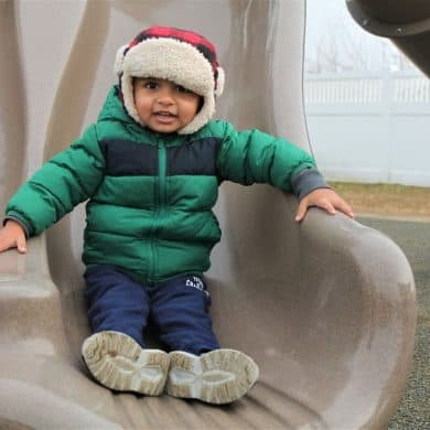 KAUF Child Smiling on Toddler Slide