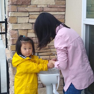 Parents help wash hands during drop offs. To help prevent the spread of germs.
