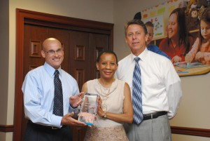 Franchisee Margaret Harper receives award from Kiddie Academy Executive Chairman Michael Miller (L) and President Gregory Helwig