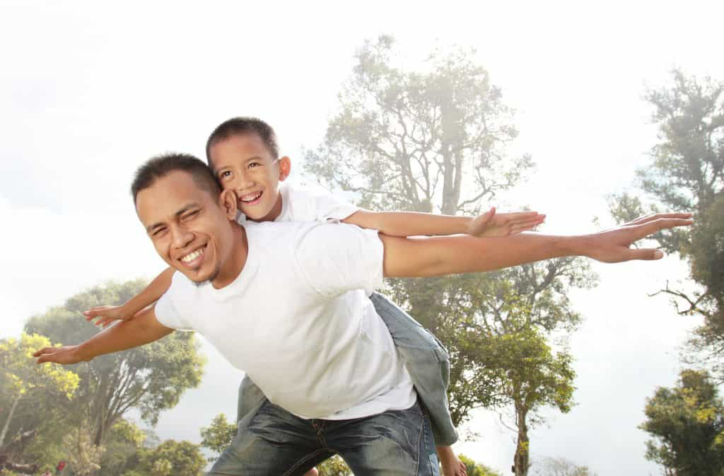 father giving his son piggyback ride outdoors against sky