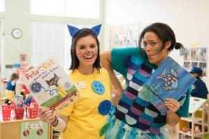 Kiddie Academy Pre-School teachers, Amy Sauers (left) and Brie Brown (right), dress up and pose with their favorite children's book in celebration of Read Across America Day