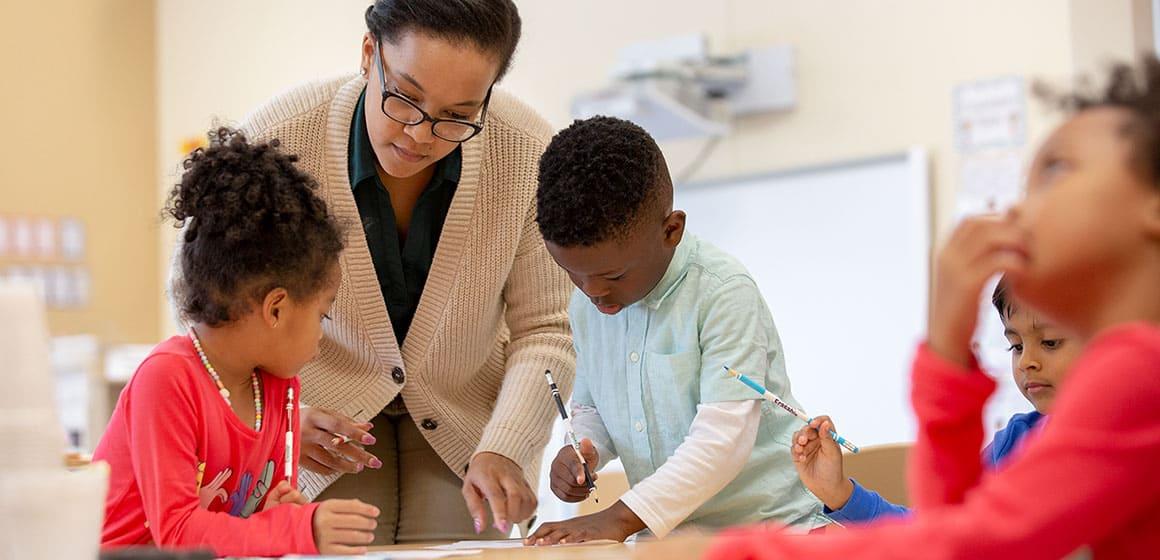 A teacher helping children with writing