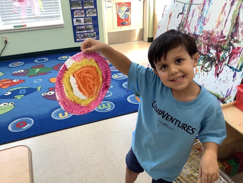 kiddie academy student showing artwork
